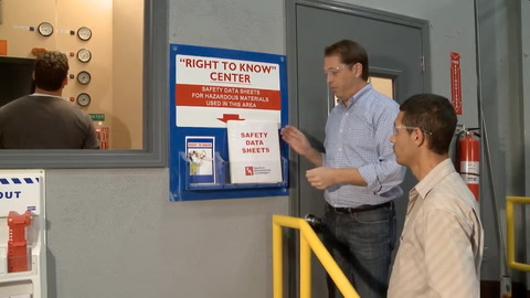 Screen shot of video with a man gesturing to a Safety Data Sheets book to another man