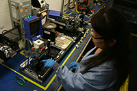 Assembly worker Tonia Moua removes the jacket off of a ribbon cable to be soldered to a printed circuit board.