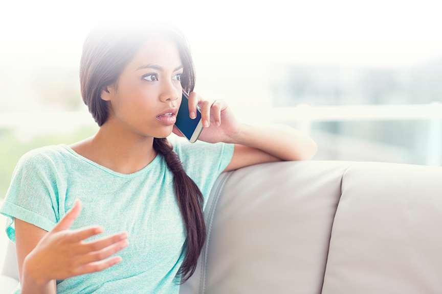girl sitting on sofa with mobile phone in left hand held up to left ear